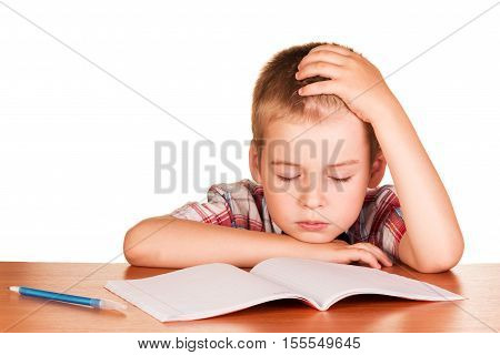 Tired boy sitting at the table fell asleep on exercise book isolated on white background.