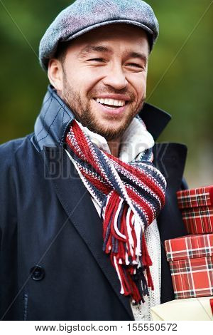 Portrait of charismatic laughing man holding gift boxes