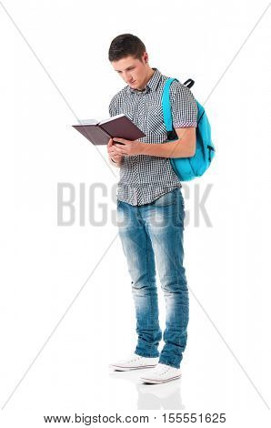 Handsome teen boy with backpack and notepad, isolated on white background. Full length portrait of a young man reading book. Adult male student with school bag carrying text books.