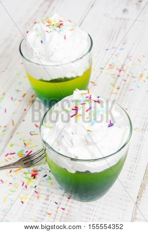Multicolored jelly with whipped cream and candy topping