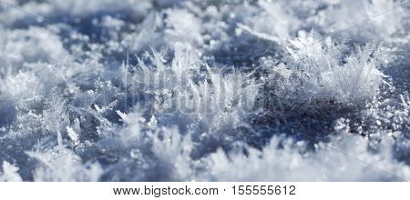 blue crystals of snow closeup with shallow depth of field