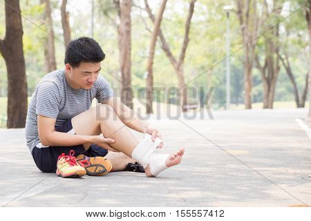 Sports injury. Man with pain in ankle and bandaging foot