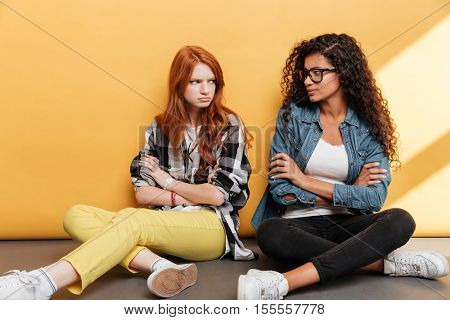 Two sad offended young women sitting with arms crossed over yellow background