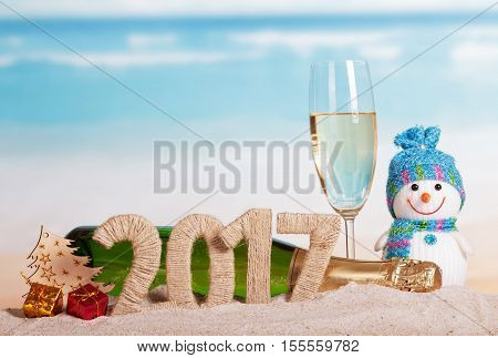 Figures 2017, a bottle of champagne and glass, snowman, Christmas tree, Christmas gifts in the sand against the sea.