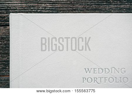 Hard cover on white leather book with text 'WEDDING PORTFOLIO'