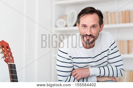 Being at home. Cheerful positive nice man standing in the room and looking at you while smiling
