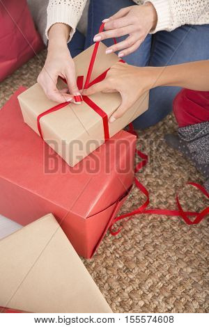 Woman's hand tying red ribbon bow on gift box