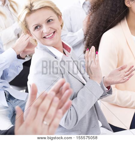 Group of coworkers on business meeting clapping their hands