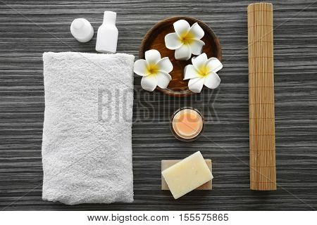 Spa set with nutrient cream, soap and flowers on wooden background