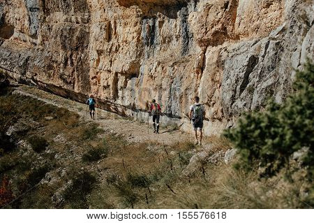 group of tourists climbers walking trail along steep cliff. travel in mountains