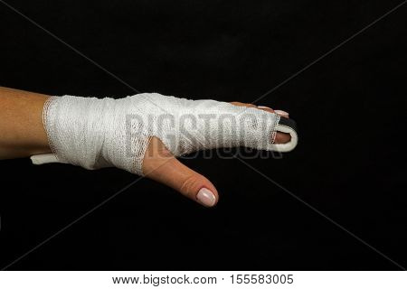 Women hand with finger crossed over rail stabilizing wrapped in elastic bandage injury finger on a black background. Close horizontal view.