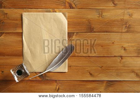Inkwell with feather and sheet of paper on wooden background