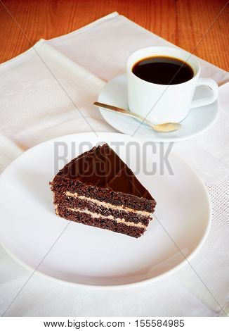 Chocolate cake on the white plate with cup of coffee. Selective focus on cake