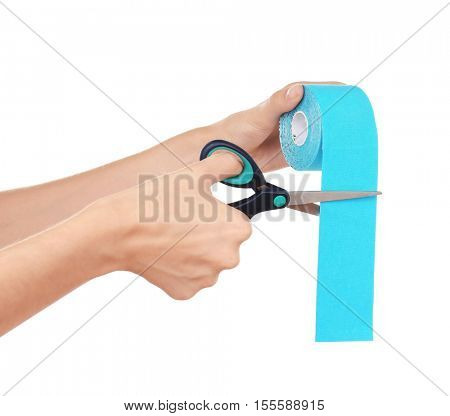 Woman cutting physio tape rolling on white background