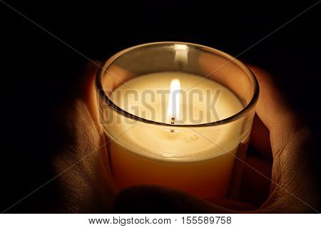 Male hands holding a candle in the transparent glass shining in the darkness as a symbol of contemplation, meditation and calmness