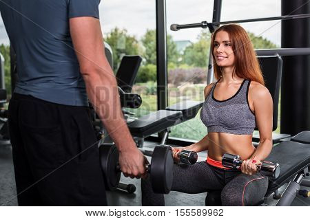 happy cutie athletic girl , execute exercise with dumb-bells and smile, in sport-hall