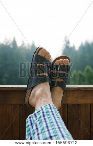 Relaxing at hotel balcony in misty morning man enjoying quiet autumn daybreak.