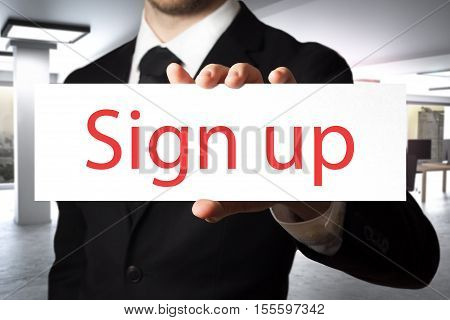 businessman in office holding sign sign up