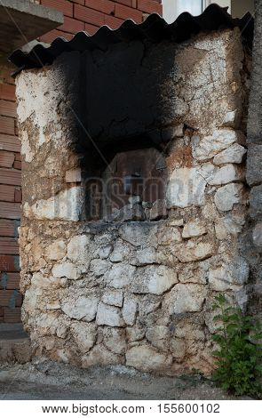 Old traditional balkan abandoned firewood oven with natural stones.