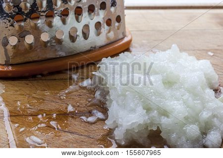 Grated onion near metal standing grater on wooden cutting board closeup