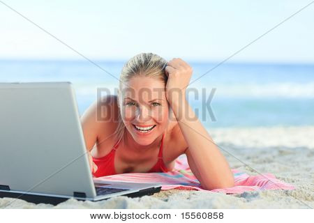 Lovely woman working on her laptop at the beach