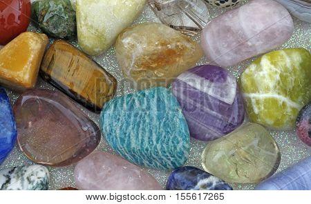 Close up of Healing Crystals - Various tumbled stones on an iridescent background including amazonite, ametrine, citrine, rose quartz, emerald, smokey quartz, jasper and tigers eye