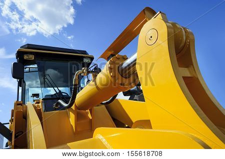 Bulldozer, huge yellow powerful construction machine with big scoop, focused on hydraulic piston arm, heavy industry, blue sky and white clouds on background