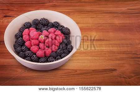 Ceramic plate with heart shaped berries on the left of the wooden table with clipping path. Top side view. Top side view.
