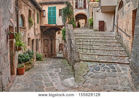 Sorano, Grosseto, Tuscany, Italy: picturesque corner with old staircase, alley, underpass and plants in the Tuscan medieval village