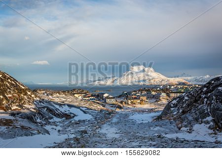 Daylight view to the distant suburb of Nuuk Sermitsiaq mountain in the background