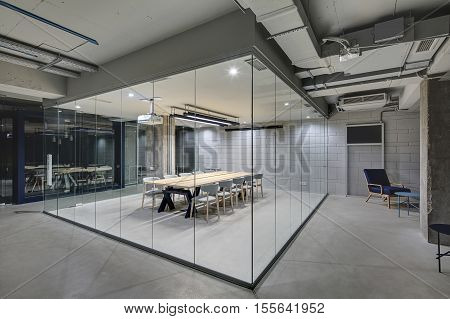 Luminous conference zone in the office in a loft style with brick walls and concrete columns. Zone has a large wooden table with gray chairs and glass walls. Above the table there is a projector.