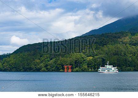 Red Torii Gate And Tourist Boat Cruising Ashi Lake