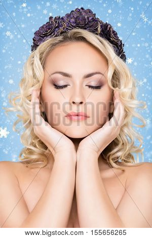 Beauty portrait of attractive blond girl with curly hair and a beautiful headband over winter  background. Christmas concept.