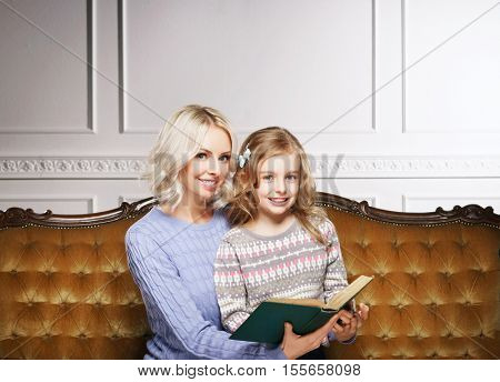 Mother and daughter reading book at home. Fairy tail concept.