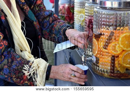 Woman's hand unscrews the faucet which drops the fresh water into a glass. Filling A Glass Of Water From Tap. Jugs full of with water and fruits orange strawberry lemon.