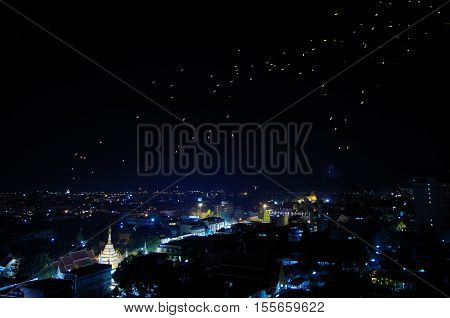 Time lapse of lanterns ascending into a dark Asian sky over the blueish city night lights