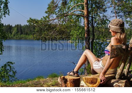 a young happy woman sitting outdoors on bench infront of a lake with a seaview