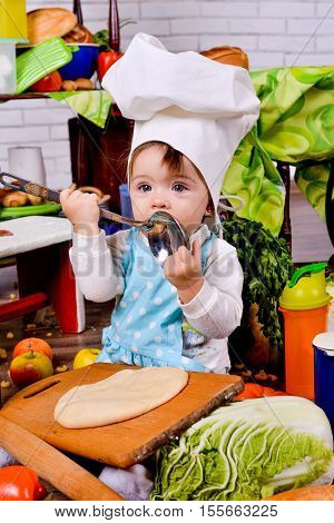 Cute girl in white cap cook standing beside wooden table and playing