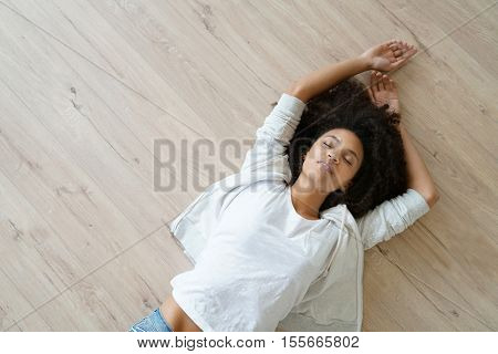 Upper view of woman lying on the back on wooden floor
