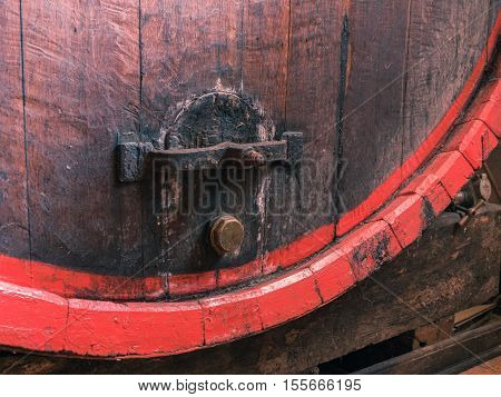 Picture of a brown wine barrel stacked in the old cellar of the winery. Background of the wooden barrel made of brown planking close up.