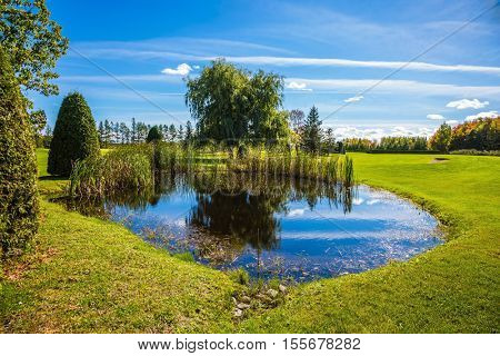 Concept Golf tourism. Small quiet pond with water mirror reflecting the blue sky. Phenomenally beautiful park with autumn foliage