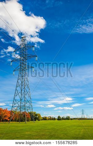 Electricity transmission air-line support. Red and green autumn foliage. Shining sunny day in French Canada