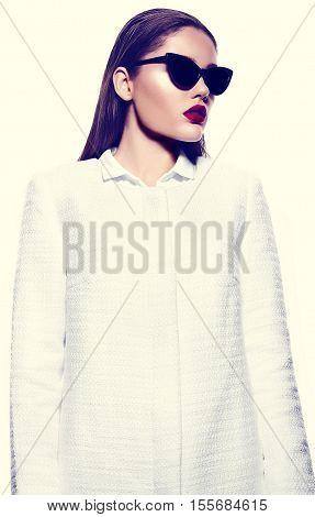 High fashion look.glamor closeup portrait of beautiful sexy stylish brunette young woman model with bright makeup with red lips in white coat jacket in sunglasses