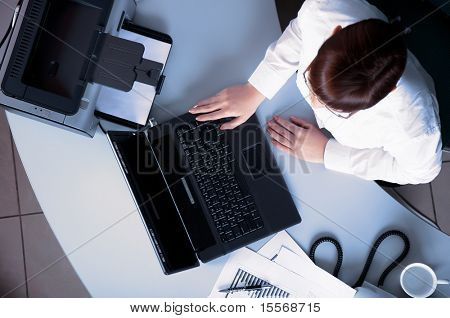 Young business woman working on a laptop at his desk in the office