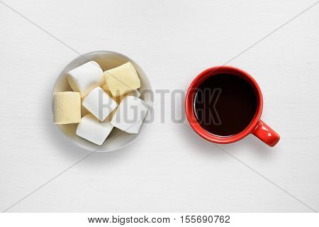Marshmallow and coffee cup on white table