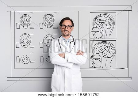Interested in brain. Inspired handsome man smiling and folding his hands while standing against the painted wall.