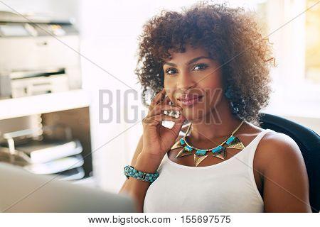 Black female entrepreneur at office sitting at desk smiling to camera