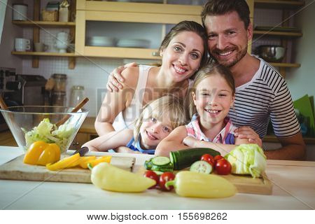 Portrait of happy family leaning on kitchen worktop at home