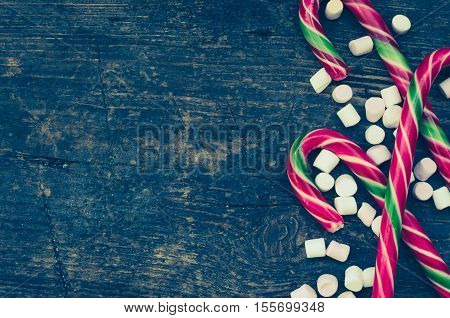 Striped Christmas candy canes with mini marshmallow on shabby chic wooden background with place for text. Red and green candy canes on weathered wooden board. Christmas Background. Copy space.