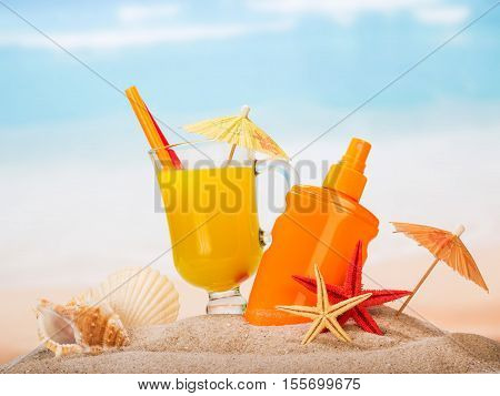 A glass of juice, sunscreen, umbrellas, starfish and shells in the sand against the sea.